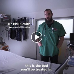 Dr Phil Smith from Westmead Hospital standing next to a hospital bed with subtitle 'This is the bed you'll be treated in'. and play button superimposed