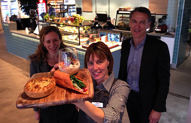 Three people standing together in a retail food outlet. One is holding a wooden board of healthy food items.