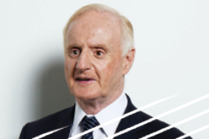 Headshot of Professor Ron McCallum standing in front of a white wall wearing a white shirt, black and blue striped tie, black blazer and smiling. A former senior advisor to the Royal Commission for two years.
