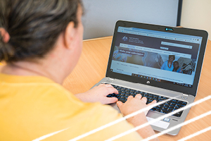 A women wearing a yellow top is typing on a laptop. On the screen is a page within the Disability Royal Commission website.